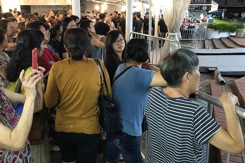 A large crowd of mourners outside the wake area last night. The public memorial for actor Aloysius Pang will be held at 82A MacPherson Lane from noon today to noon tomorrow. Mr Pang's close friends and relatives paying their last respects at the wake