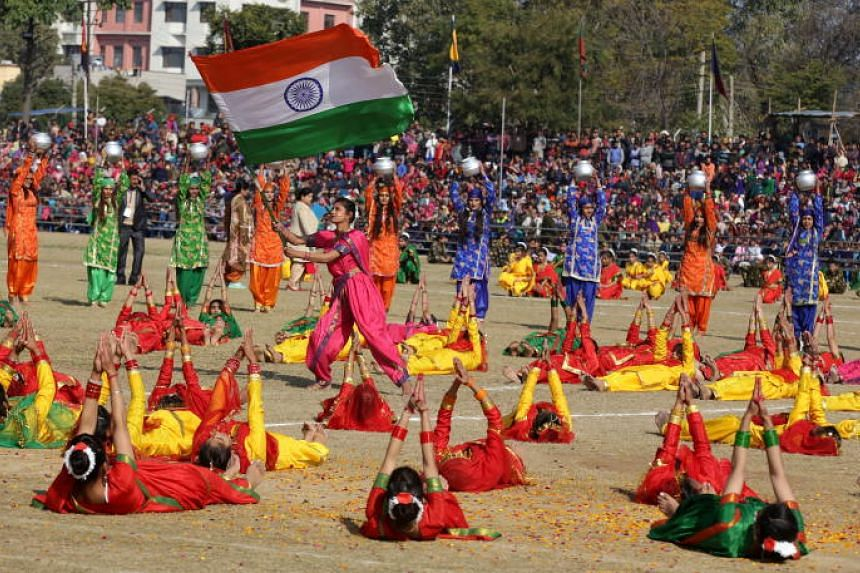 Children waving an Indian flag as they perform a cultural dance during the country's 70th Republic Day celebrations in Jammu, Kashmir, on Jan 26, 2019.