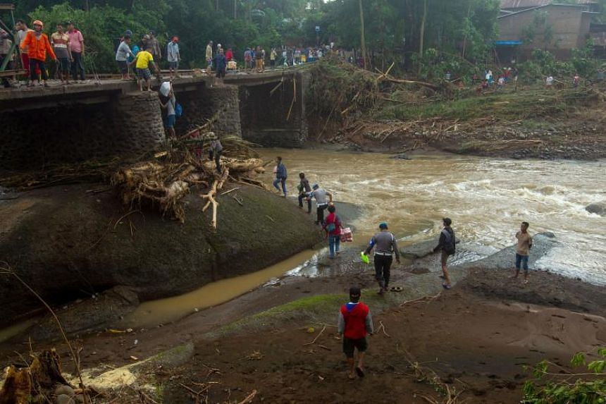 Indonesian rescuers repairing a bridge following a landslide in Gowa, after heavy rains and strong winds pounded the southern part of Sulawesi island, on Jan 25, 2019.