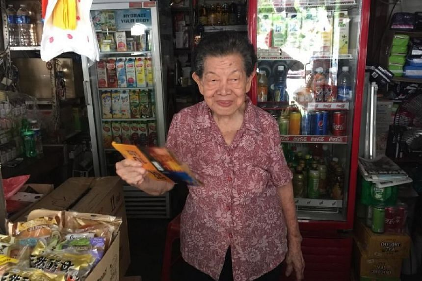 A shop owner in Shunfu cooling herself with a pamphlet.