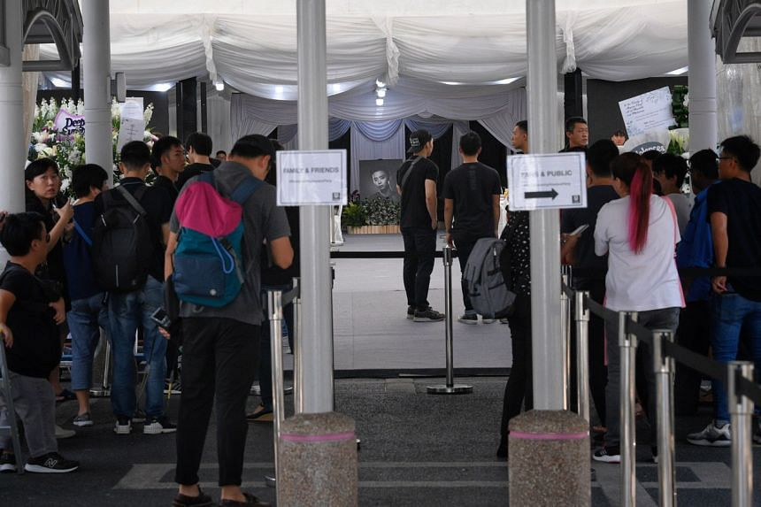 Members of the public (right) queueing in line to pay their respects at 10.30am.