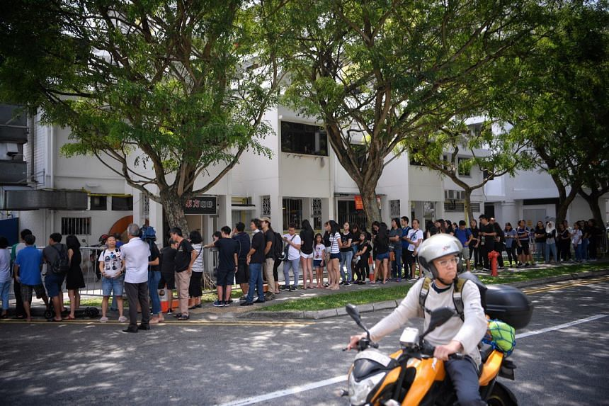 Members of the public queueing to pay their respects to Mr Aloysius Pang. The queue snaked around the block in MacPherson Lane.