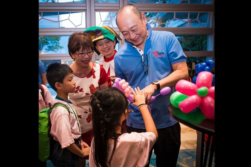 UOB deputy chairman and CEO Wee Ee Cheong and Ms Denise Phua, mayor of the Central Singapore District, giving out sculpted balloons to children residing in Kampong Glam.