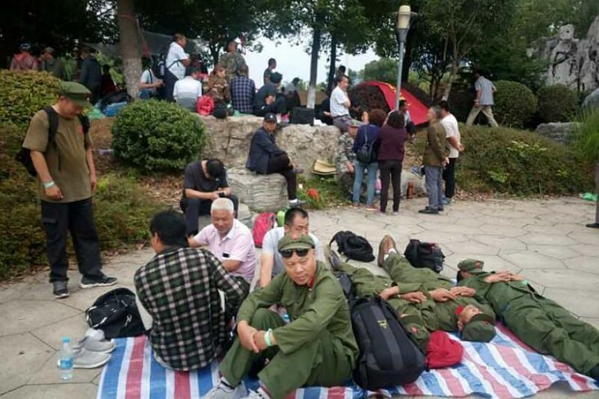 Chinese military veterans sit on the ground during a demonstration in Zhenjiang, China, on June 22, 2018.