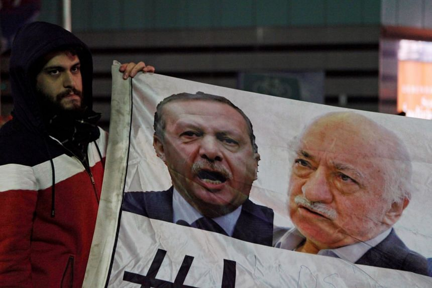 A demonstrator holding pictures of Turkey's Prime Minister Tayyip Erdogan and Turkish cleric Fethullah Gulen (right), during a protest against Turkey's ruling AK Party in Istanbul.