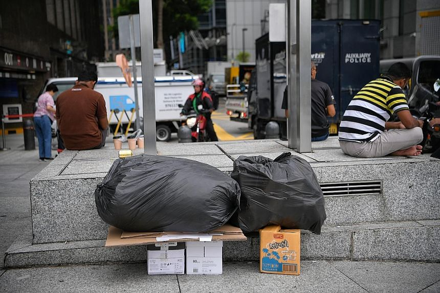 Two cartons filled with documents left unattended outside a building in Bonham Street for disposal. The practice raises questions of whether businesses here are too lax about proper disposal of documents.
