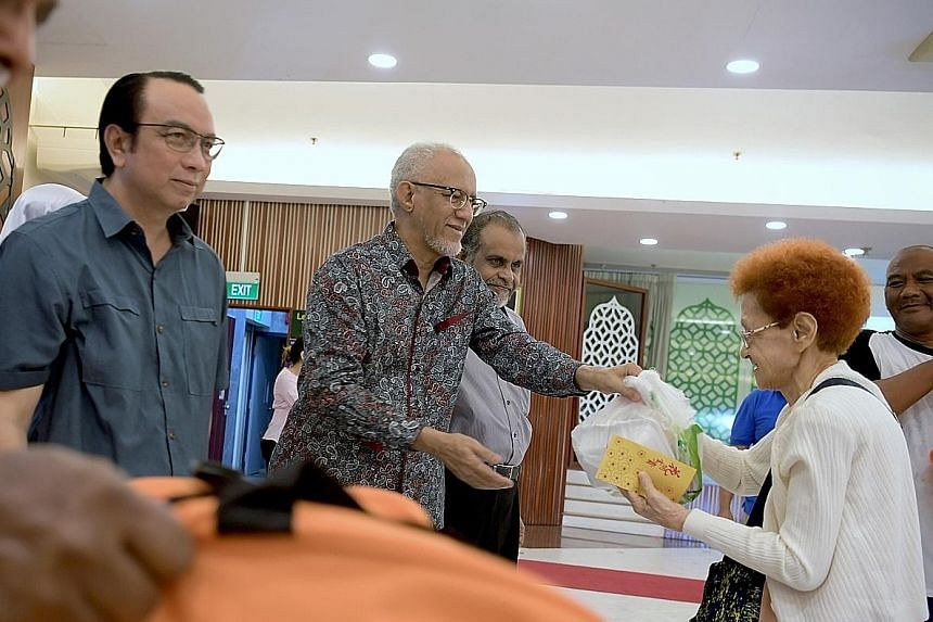 Guest of honour Mohamed Abdullah Alhabshee, President Halimah Yacob's husband, presenting food items to a Jamiyah Singapore beneficiary at the event yesterday. He is flanked by the president of Jamiyah Singapore, Dr Mohd Hasbi Abu Bakar (far left), a