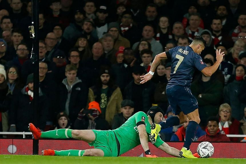 Manchester United forward Alexis Sanchez takes the ball around Arsenal goalkeeper Petr Cech before scoring the opening goal in the 3-1 FA Cup fourth-round victory at the Emirates Stadium on Friday.