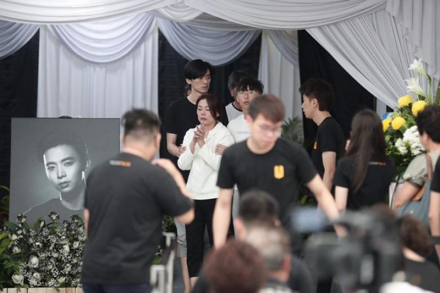 Home-grown actor Aloysius Pang's mother (in white top), supported by her sons Kenny (left) and Jefferson, at the wake in MacPherson on Jan 27, 2019.