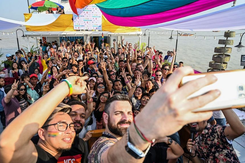 Members of the LGBT community dance and take selfies under rainbow flags displayed on a boat during the Pride Boat Parade.