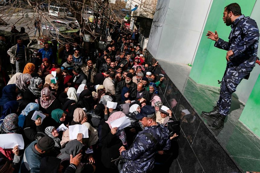 Security forces loyal to Hamas organise people as they queue in Gaza City to receive financial aid from the Qatari government.