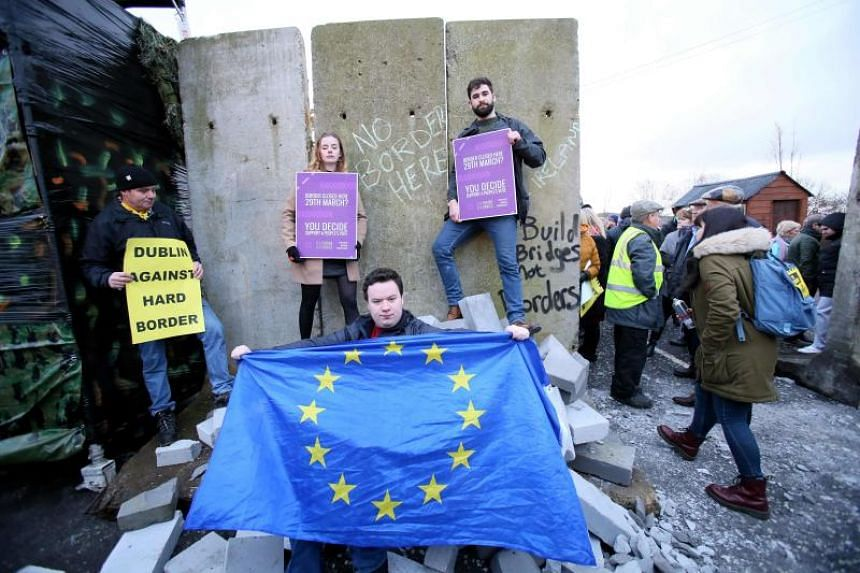 A pro-EU activist holds an EU flag after protesters smashed through a mock wall during a demonstration on a road crossing the border between Northern Ireland and Ireland in Newry, Northern Ireland, on Jan 26, 2019.