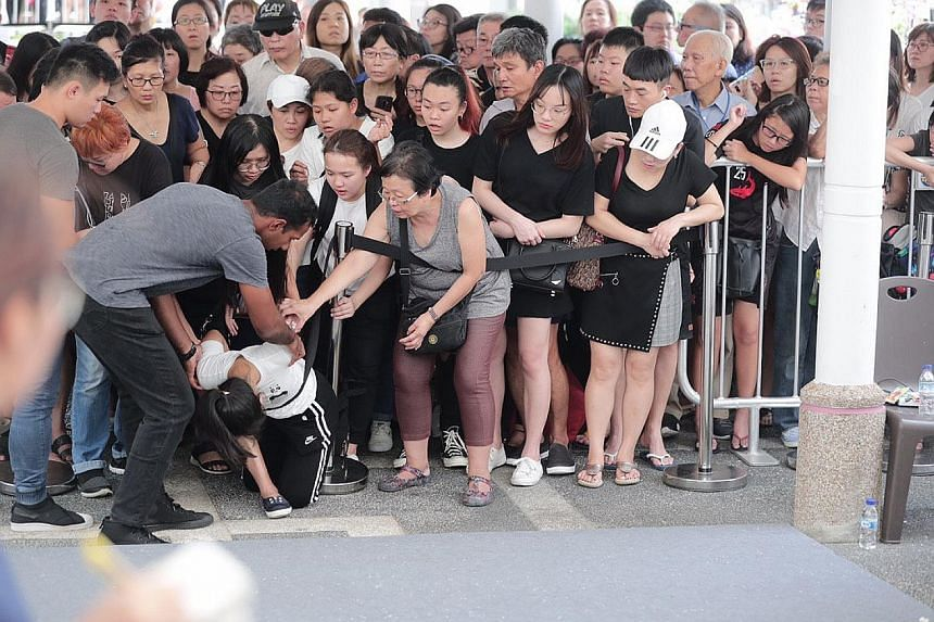 Actress Jayley Woo, Mr Pang's girlfriend, placing her hand on veteran actor Chen Shucheng's shoulder as they walk behind the hearse with other friends and relatives. Pall bearers from the Singapore Armed Forces carrying the casket of Corporal First C