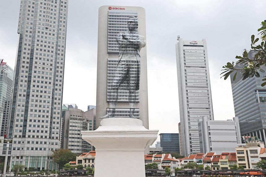 The white, polymarble statue of Sir Stamford Raffles by the Singapore River has been partially painted over to blend in with the OCBC Centre building across the water.