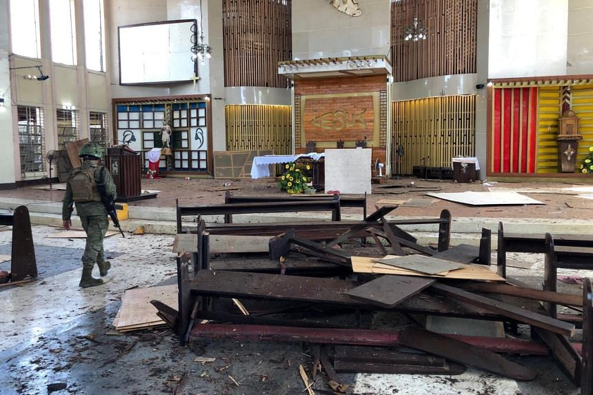 A Philippine Army member walks inside a church after a bombing attack in Jolo, Sulu province, Philippines, on Jan 27, 2019.