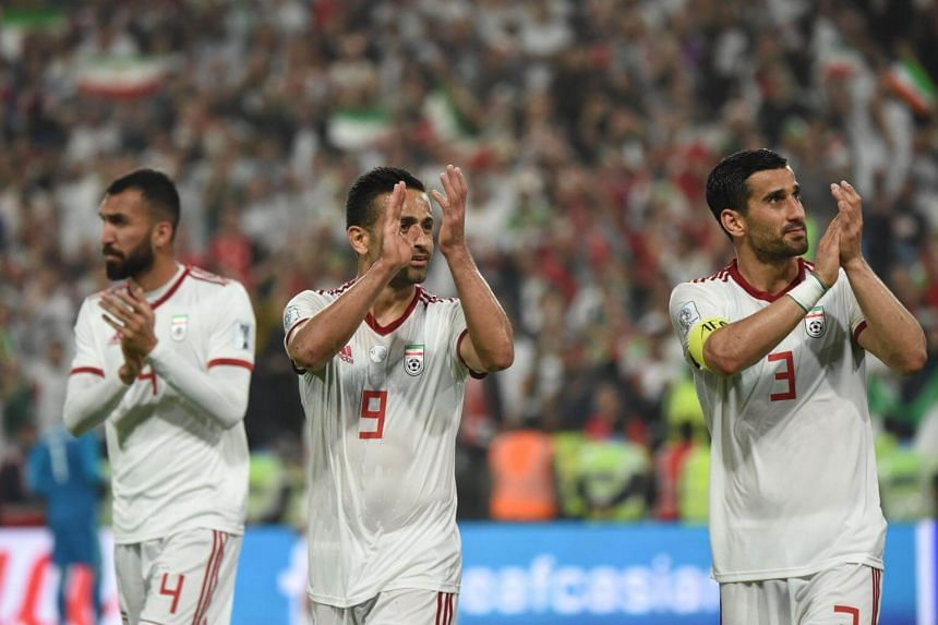 (From left) Iran's defender Roozbeh Cheshmi, midfielder Omid Ebrahimi and defender Ehsan Haji Safi celebrate their win during the 2019 AFC Asian Cup quarter-final football match at the Mohammed Bin Zayed Stadium Stadium in Abu Dhabi, on Jan 24, 2019.
