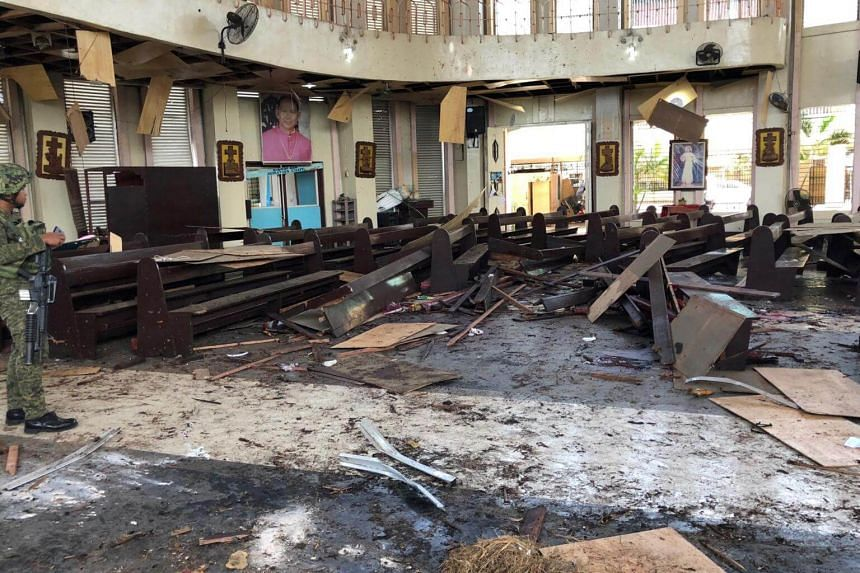 A Philippine Army member inspects the damage inside a church after a bombing attack in Jolo, Sulu province, on Jan 27, 2019.