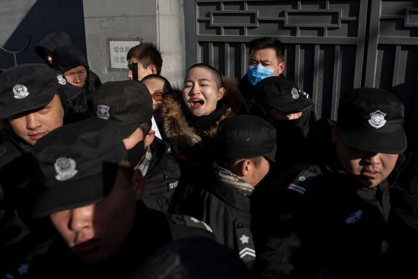 Chinese police and security personnel surrounding Li Wenzu (centre), wife of prominent Chinese human rights lawyer Wang Quanzhang, in Beijing on Dec 28, 2018. She shaved her head to protest against the treatment of her husband, who was sentenced to 4