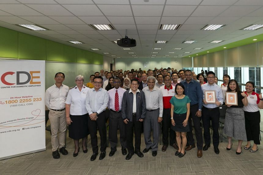 Executive director of the Centre for Domestic Employees (CDE), Shamsul Kamar Mohamed Razali (in red) and chairman of the CDE, Yeo Guat Kwang, (in a jacket) posing for a group picture with representatives of the CDE's partner organisations.