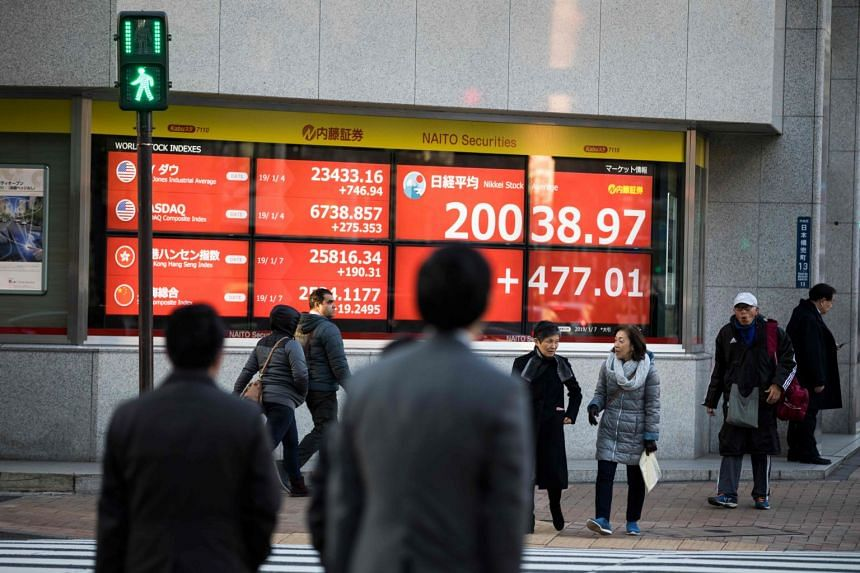Pedestrians crossing a street in front of a stock indicator board displaying share prices of the Tokyo Stock Exchange.