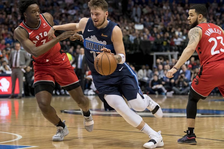 Dallas Mavericks forward Luka Doncic (77) drives to the basket past Toronto Raptors forward OG Anunoby (3) and guard Fred VanVleet (23) during the second quarter.