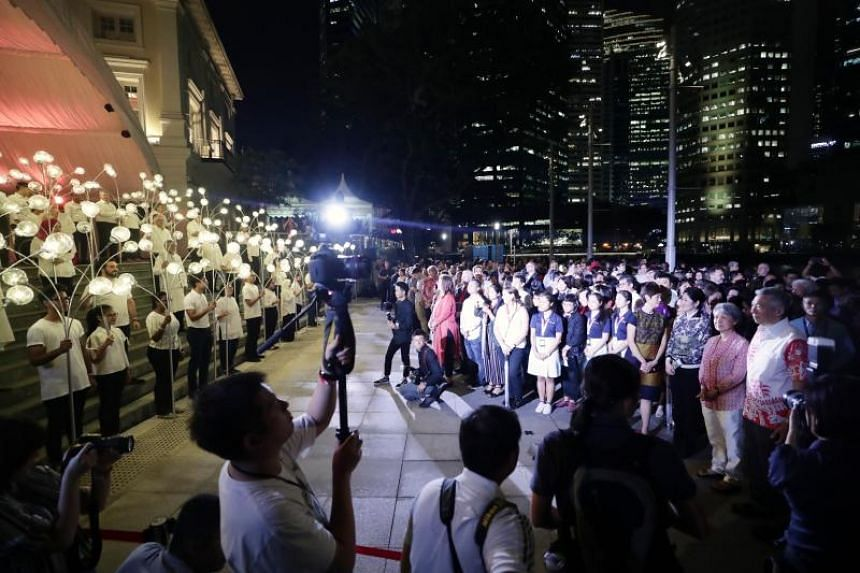 Prime Minister Mr Lee Hsien Loong (far right, in white) and Mdm Ho Ching and guests looking at light bearers representing different communities who made Singapore their home.