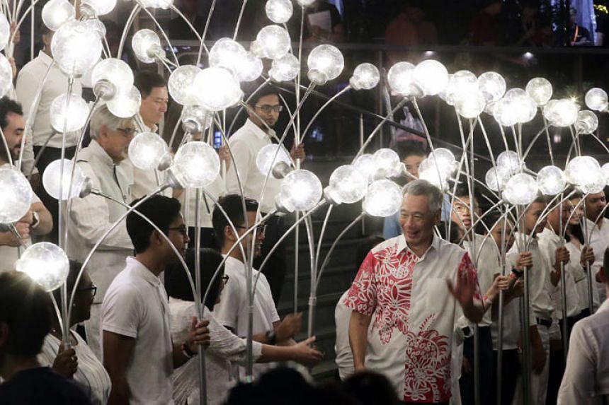 Prime Minister Mr Lee Hsien Loong standing among light bearers representing different communities who made Singapore their home at the launch of the Singapore Bicentennial.