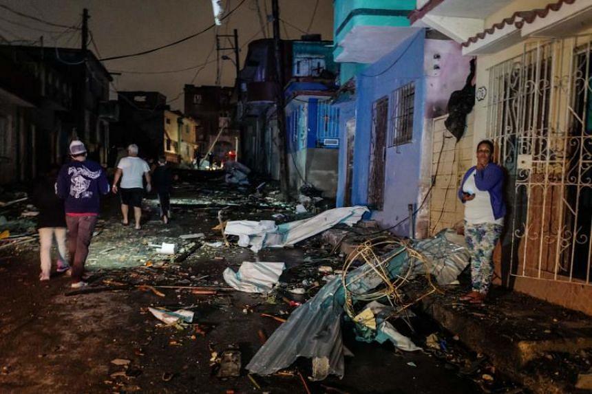 Cubans walk past debris in the tornado-hit Luyano neighbourhood in Havana early on Jan 28, 2019.