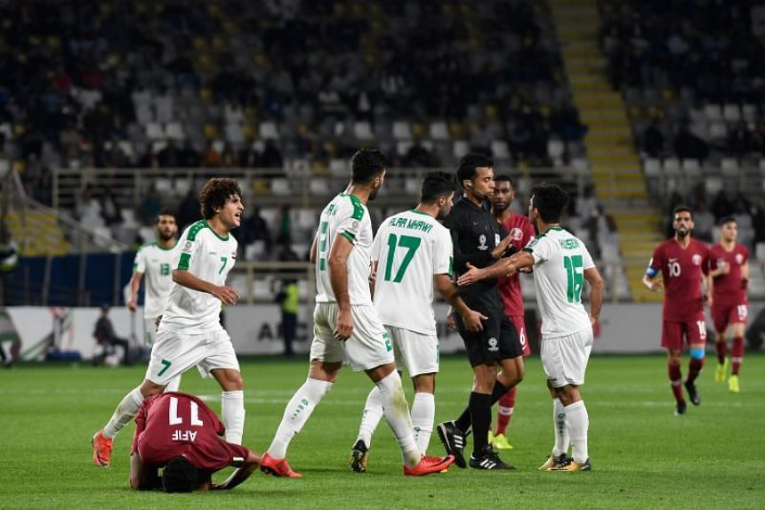 Iraq's players argue with the referee during the 2019 AFC Asian Cup match against Qatar at the Al Nahyan Stadium in Abu Dhabi on Jan 22, 2019.