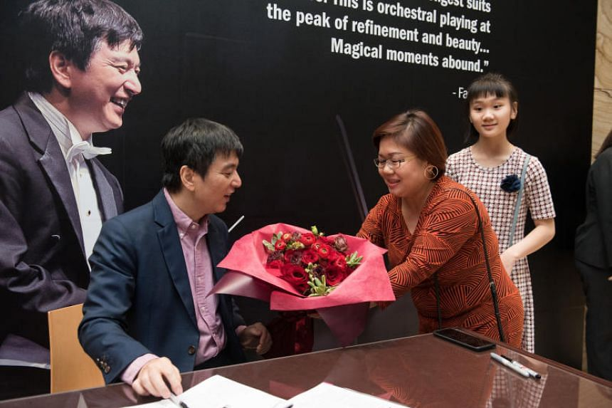 Lan Shui recieving flowers from a fan at an autograph signing after the Singapore Symphonic Orchestra Lan Shui Farewell concert.
