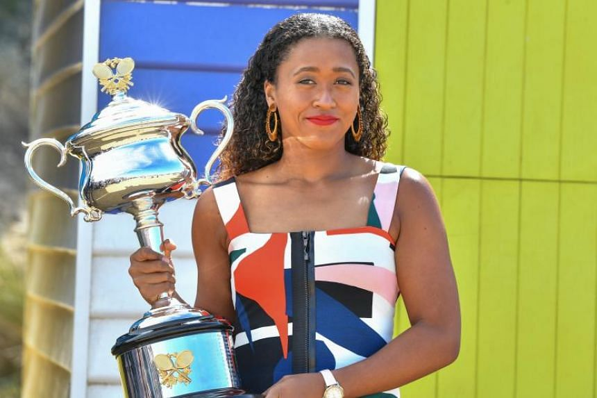 Japan's Naomi Osaka poses for photographs with the championship trophy at the Brighton Beach in Melbourne on Jan 27, 2019.