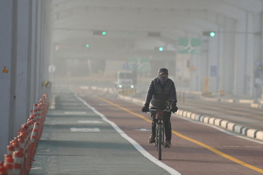 """A cyclist travels through murky air caused by pollutants known as """"fine dust"""" on Jamsu Bridge in Seoul, South Korea, on Jan 23, 2019."""