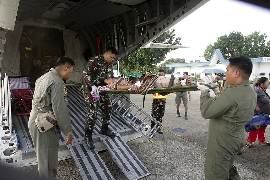 Philippine Air Force personnel transferring a victim of the twin bombing, at Edwin Andrews Air Base on Sunday.
