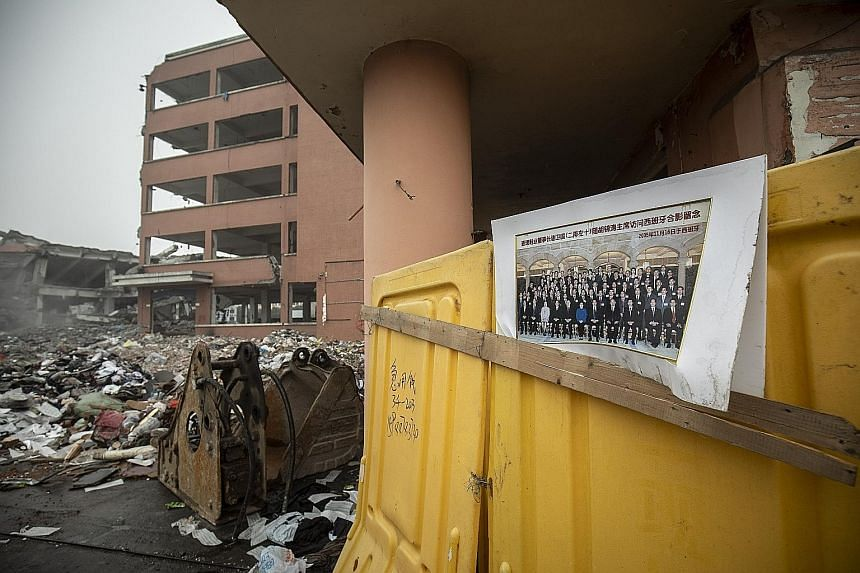 "A photograph of entrepreneurs, including the owner of a local shoe manufacturer, with then Chinese President Hu Jintao during a visit to Spain sits at an industrial complex undergoing demolition along Xiedu Avenue, which translates to ""Shoe Capital"""