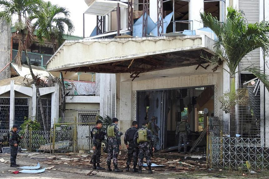 """Policemen and soldiers outside the wrecked church in Jolo, Sulu province, which was hit by two bomb attacks on Sunday. Security officials have tagged six """"persons of interest"""" from the Ajang-ajang faction of the Abu Sayyaf as the main suspects."""