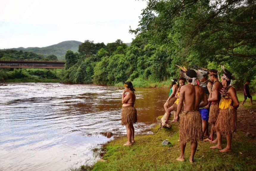 Indigenous people from the Pataxo Ha-ha-hae tribe look at Paraopeba river, after a tailings dam owned by Brazilian mining company Vale SA collapsed in Sao Joaquim de Bicas near Brumadinho, Brazil, on Jan 25, 2019.