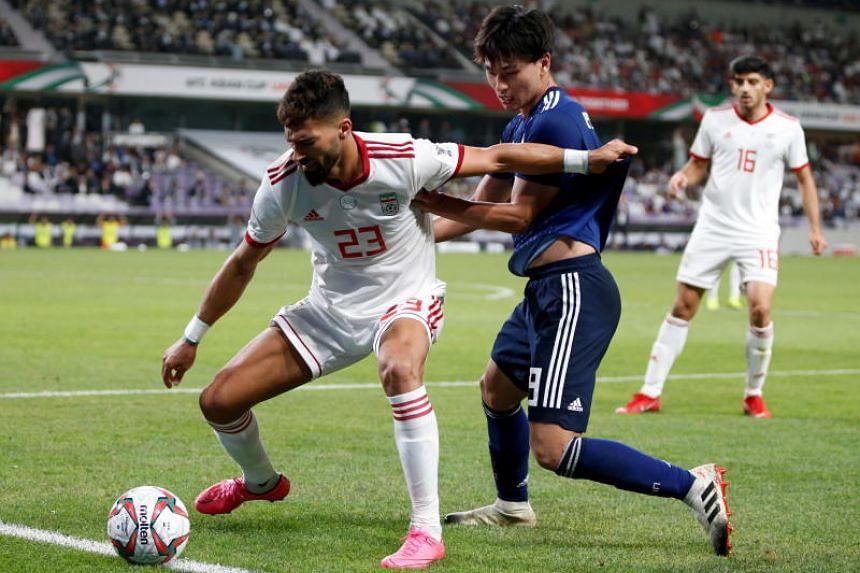Ramin Rezaeiansemeskandi (left) of Iran in action against Minamino Takumi of Japan during the 2019 AFC Asian Cup semi final round match between Iran and Japan in Al Ain, United Arab Emirates, on Jan 28, 2019.