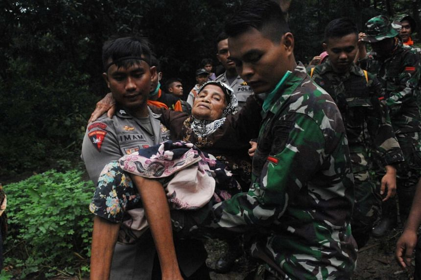 Rescue workers carrying an elderly woman following landslides in Gowa, South Sulawesi, Indonesia, on Jan 25, 2019.