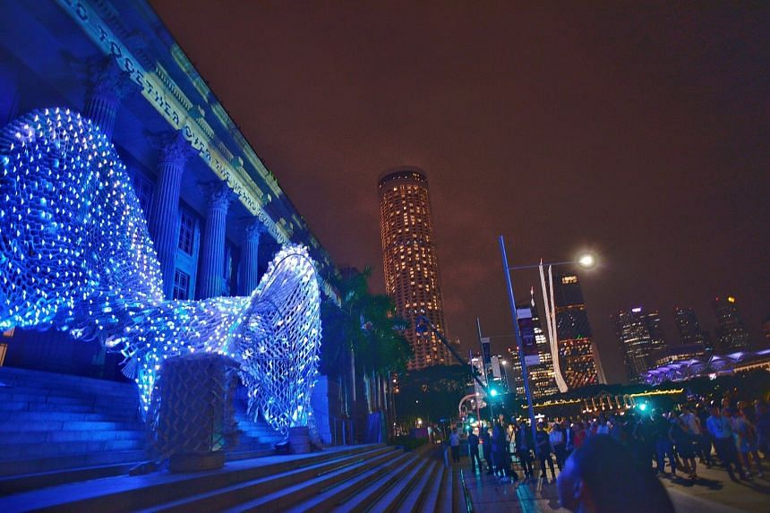 The Memory Conduit art installation (foreground). In the background, a light show called Secrets Of The Sand, Written In The Stars, Snapshots In Time plays on the National Gallery Singapore's facade.