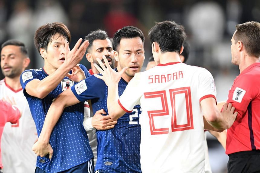 Iran forward Sardar Azmoun (second right) argues with Japan midfielder Genki Haraguchi (left) during the Asian Cup semi-final.