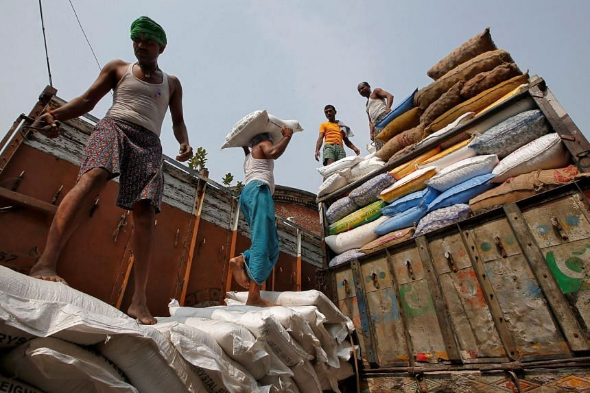 A labourer carries a sack filled with sugar to load it onto a supply truck at a wholesale market in Kolkata, India, on Nov 14, 2018.