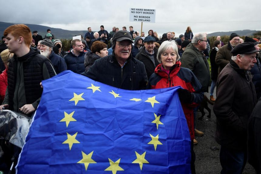 People hold a European Union flag during a protest by anti-Brexit campaigners in Carrickcarnan, Ireland, on Jan 26, 2019.