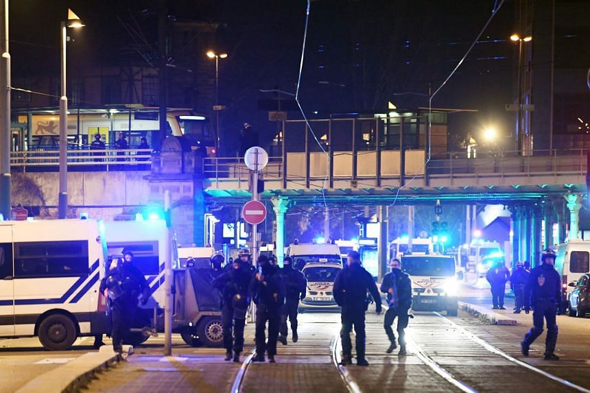 French police officers block the road near the site where Cherif Chekatt, the alleged gunman who had been on the run since allegedly killing three people at Strasbourg's popular Christmas market, has been shot dead by police on Dec 13, 2018.