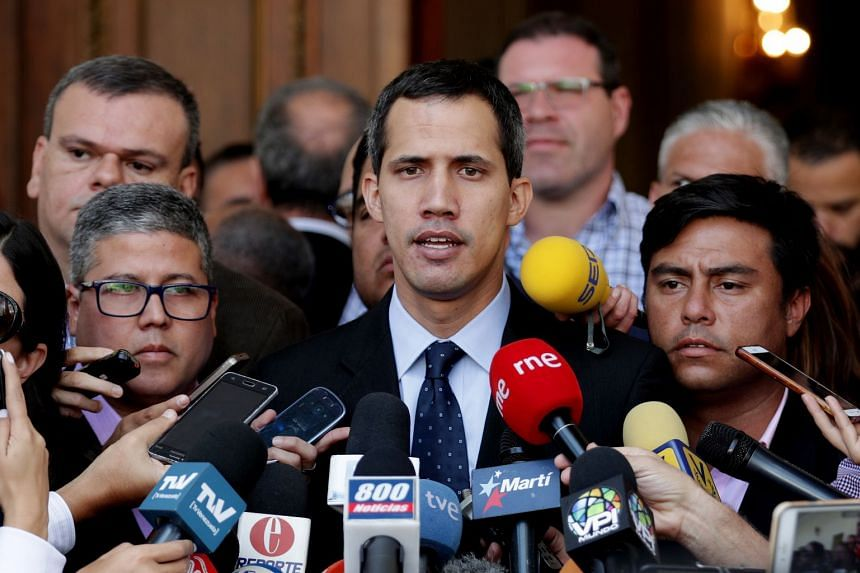 Guaido (centre) speaks to the press as he arrives at the Parliament headquarters in Caracas.