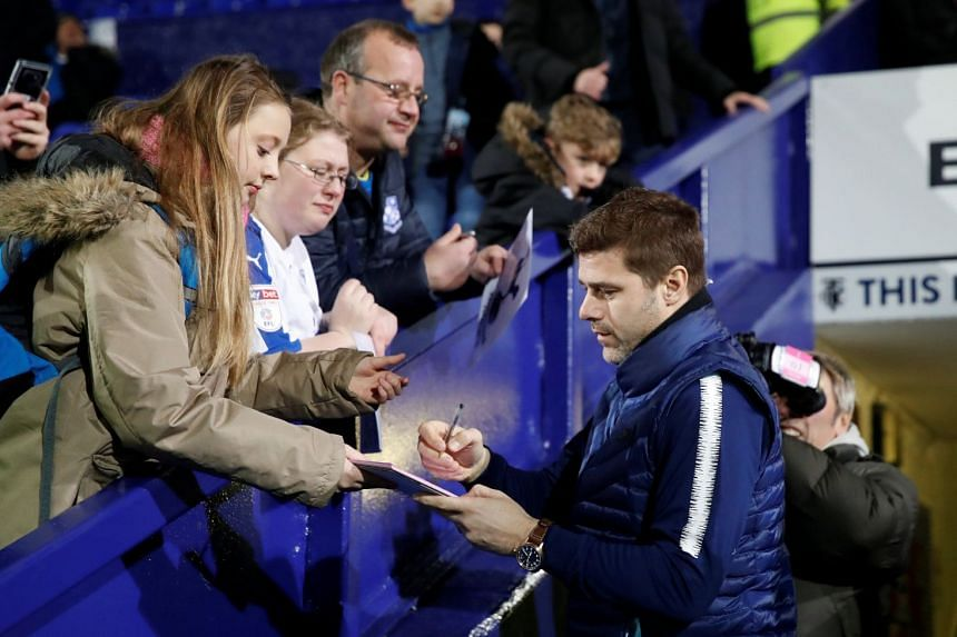 Tottenham manager Mauricio Pochettino signs his autograph for fans before a match.