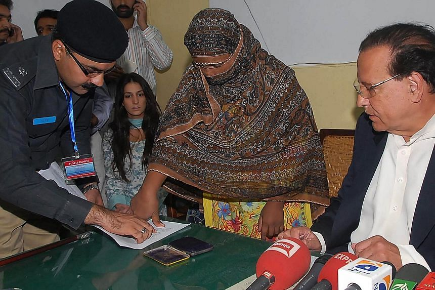 Pakistani Christian Asia Bibi putting her thumb impression as a signature on the appeal papers against her death sentence in 2010. Pakistan's Supreme Court upheld its decision to acquit the farm worker of blasphemy charges yesterday.