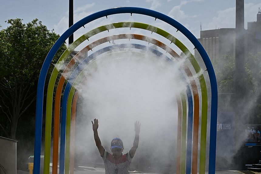 Some children having a splash at a fountain to beat the heat on Thursday, day 11 of the Australian Open tennis tournament in Melbourne. Australia's Marnus Labuschagne battling the heat at the Gabba Cricket Ground in Brisbane, where a match was held b