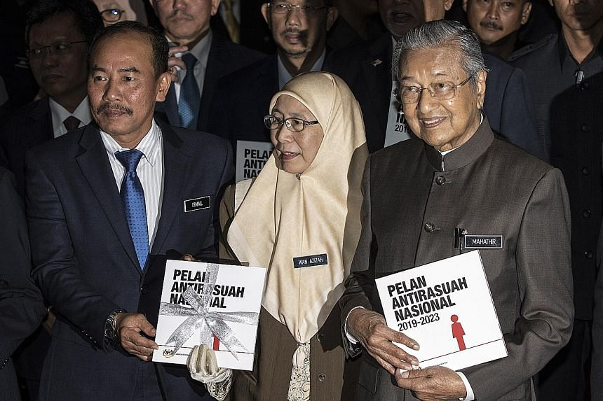 Malaysian Prime Minister Mahathir Mohamad joined Deputy Prime Minister Wan Azizah Wan Ismail and Chief Secretary Ismail Bakar to pose with a book outlining anti-corruption legislation during the launch of the National Anti-Corruption Plan in Putrajay