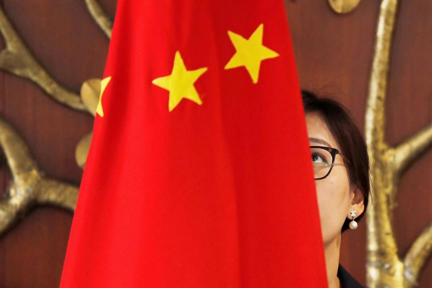 A Chinese official adjusts a Chinese flag before the start of a meeting on Dec 21, 2018.