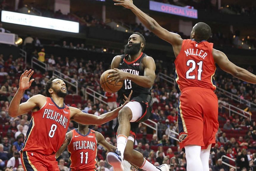 Houston Rockets'James Harden (centre) splits the defense of New Orleans Pelicans center Jahlil Okafor (left) and forward Darius Miller (right) at Toyota Center on Jan 29, 2019.